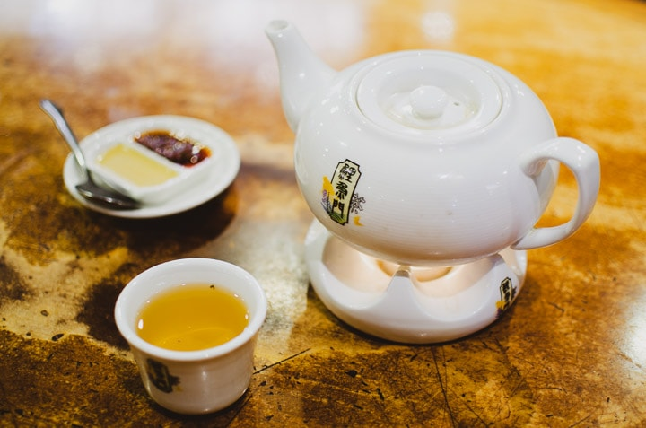 Tea pot with a tea cup and dipping sauce at dim sum