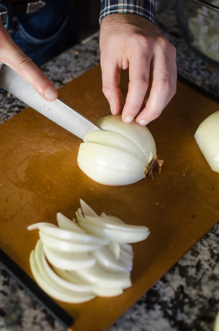 PIcture of Alex's hand slicing onions on a chopping board