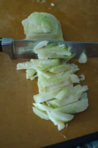 Knife cutting the sliced celeriac root into thick batonnets.