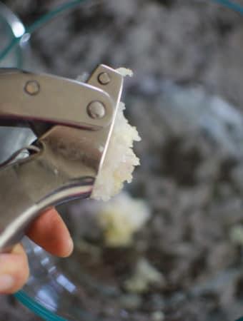 A garlic press squeezing shallot.