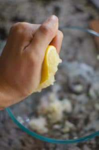 Anna's hand squeezing half a lemon.
