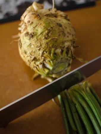 A knife chopping the leaves off celeriac on a cutting board.