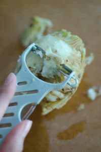 A peeler peeling the outer layer of the celeriac root.