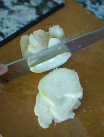 Knife slicing the celeriac root thinly.