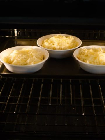 Slide the baking sheet with bowls into the oven broiler.