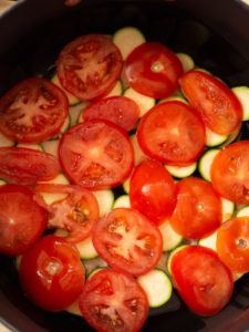 An overhead view of the soup pot to show layered ratatouille ingredients with tomatoes slices on top