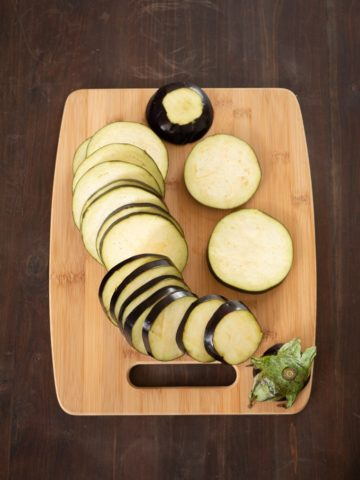 An overhead view of a chopping board to show sliced eggplant
