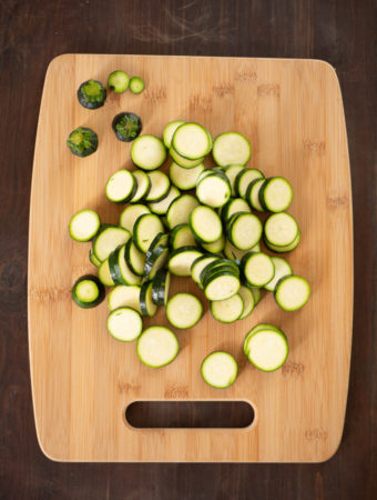 An overhead view of a chopping board to show sliced zucchini