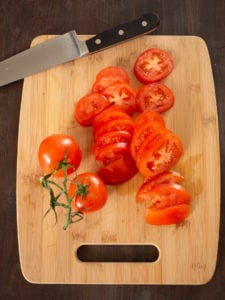 An overhead view of a chopping board to show sliced tomatoes