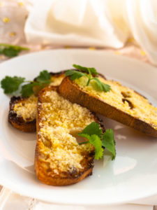 5-minute garlic bread with parmesan cheese melted on white plate with cilantro garnish