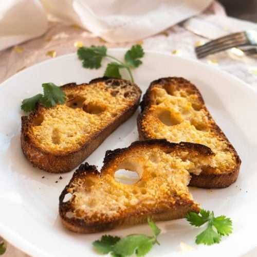 45 degree view of 5-minute garlic bread with parmesan cheese melted on white plate with cilantro garnish