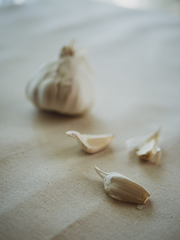 Close up look of tray of fresh raw garlic with several cloves around
