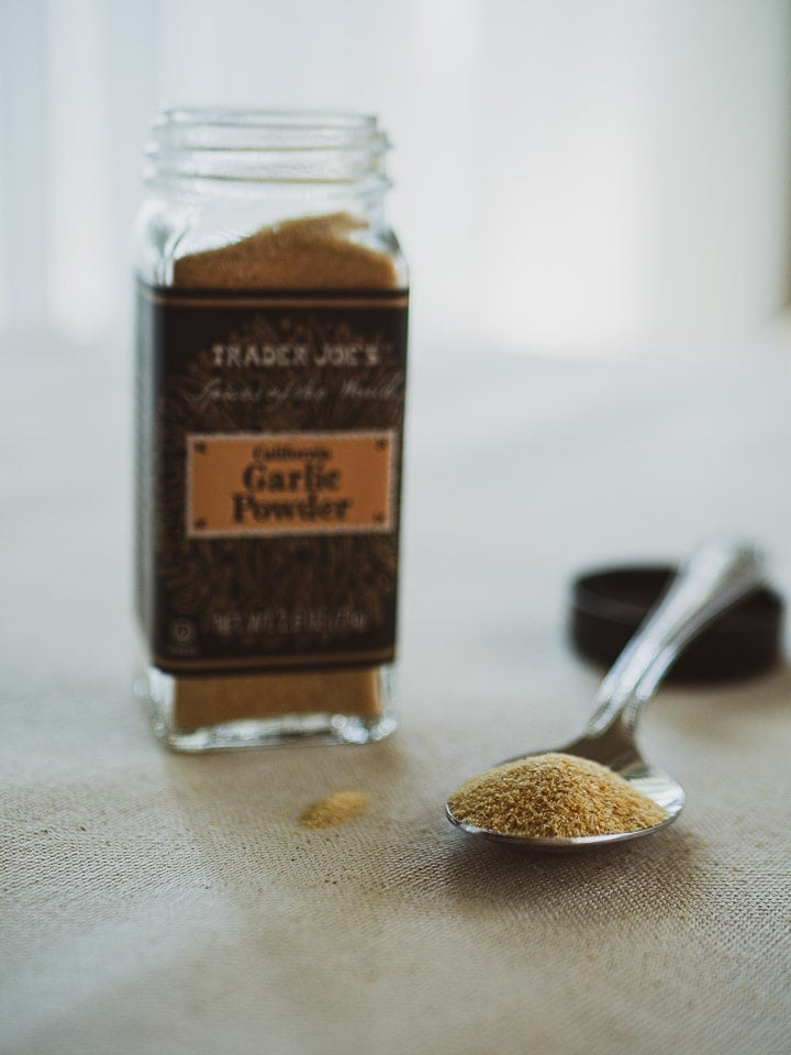 Close up of Trader Joe's garlic powder with a spoonful of garlic powder
