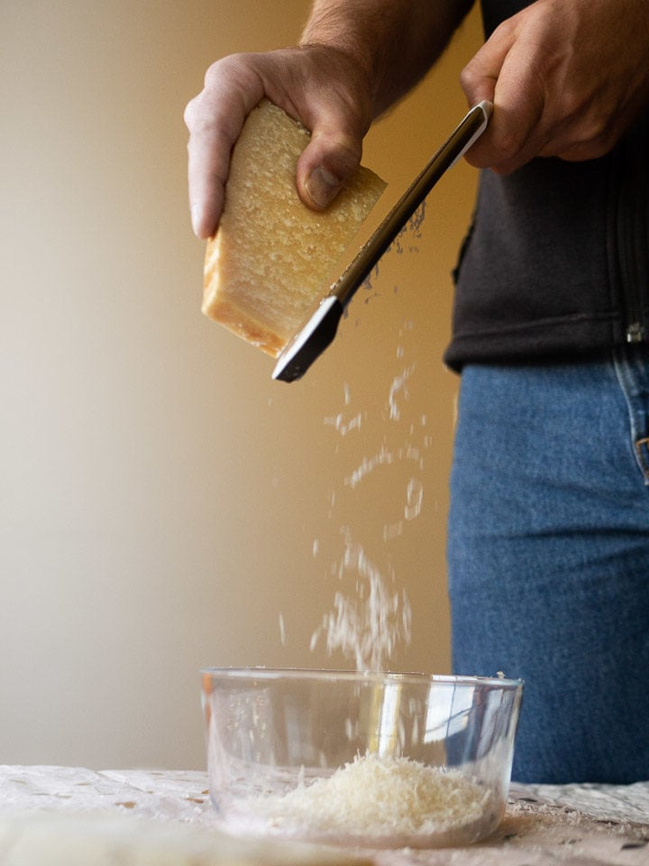 A picture of Alex grating a wedge of Parmigiano-Reggiano as the cheese falls into a glass bowl