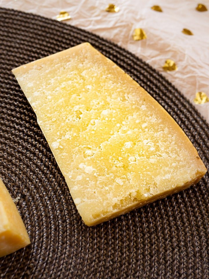 A view of a wedge of Parmigiano-Reggiano Stravecchio showing the granular texture with deep cheese crystals
