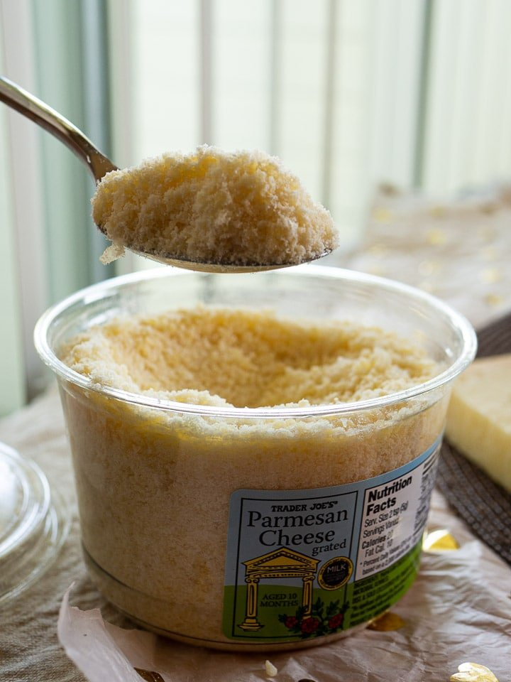 A close view of pre-grated Parmesan on a spoon with the container in the background