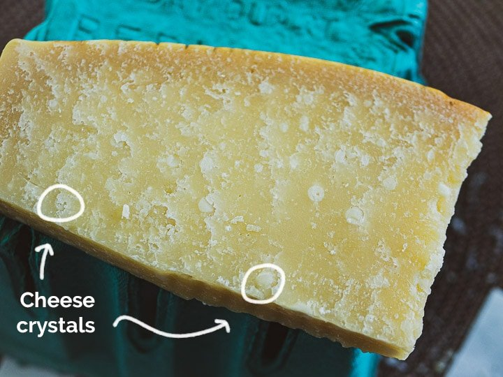 A view of a wedge of Parmigiano-Reggiano showing the granular texture with deep cheese crystals