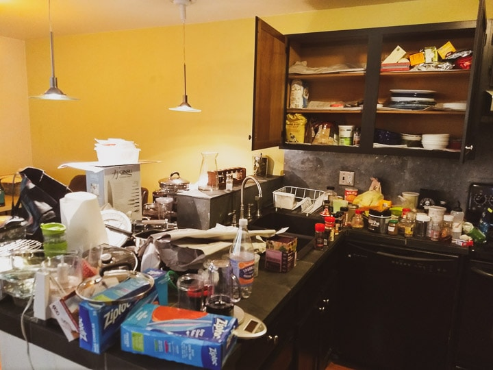 Messy moving boxes and a completely cluttered kitchen counter with barely any countertop space