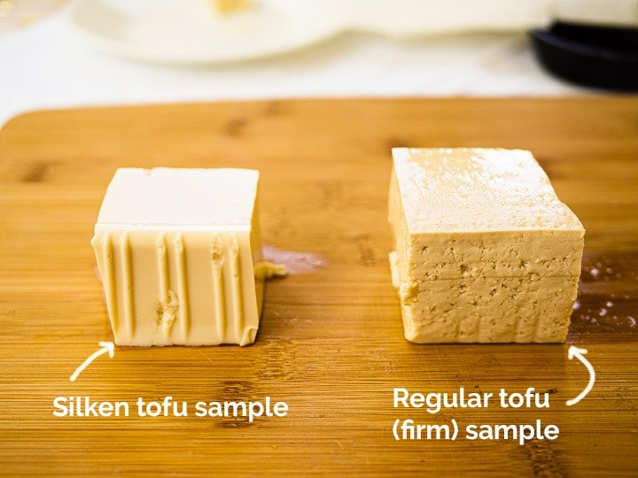 A cube of silken tofu and regular firm tofu side by side on a cutting board