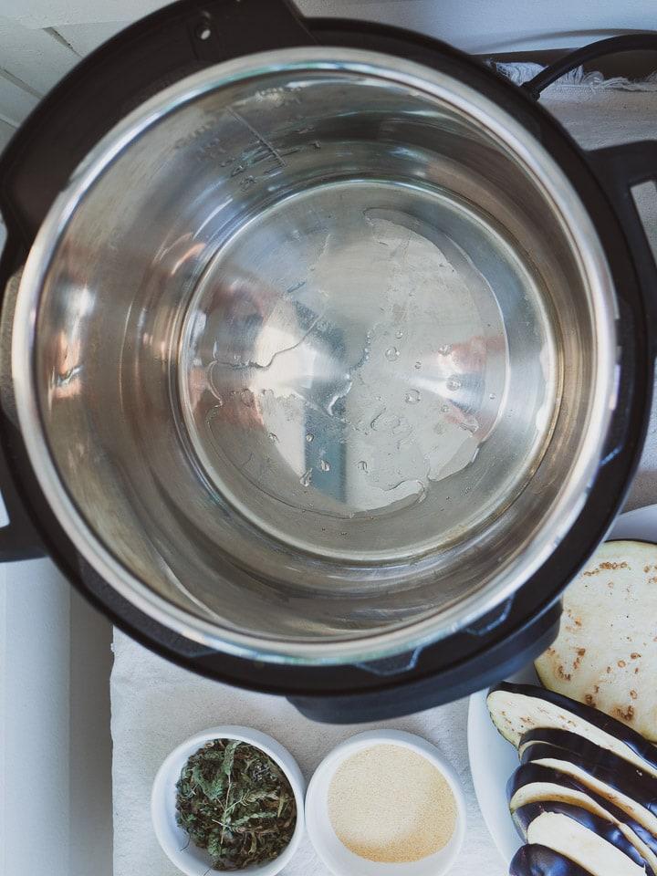 Instant Pot on sauté mode heating up hot oil for ratatouille recipe