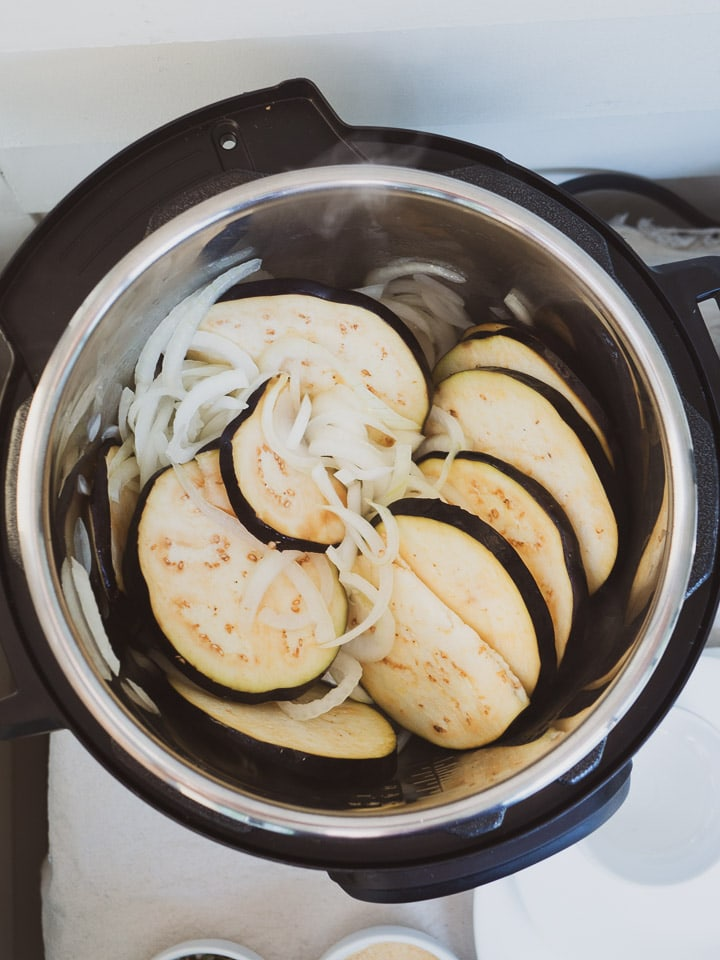Instant Pot on sauté mode heating sliced onions and eggplant for ratatouille recipe