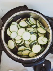 Instant Pot on sauté mode heating sliced zucchini for ratatouille recipe