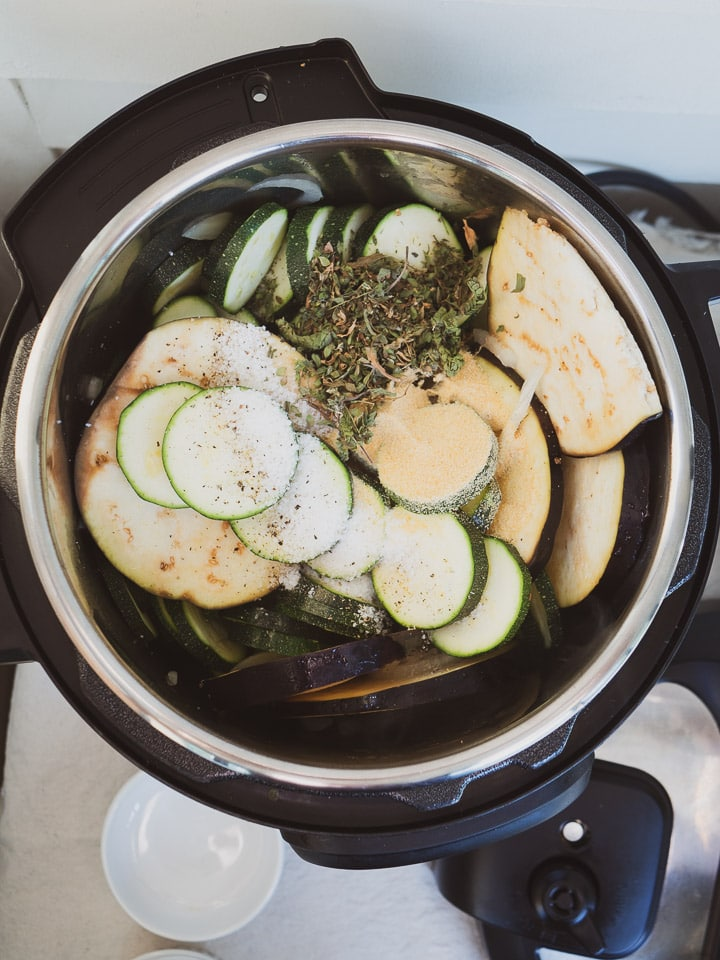 Instant Pot on sauté mode heating sliced zucchini and dried herbs for ratatouille recipe