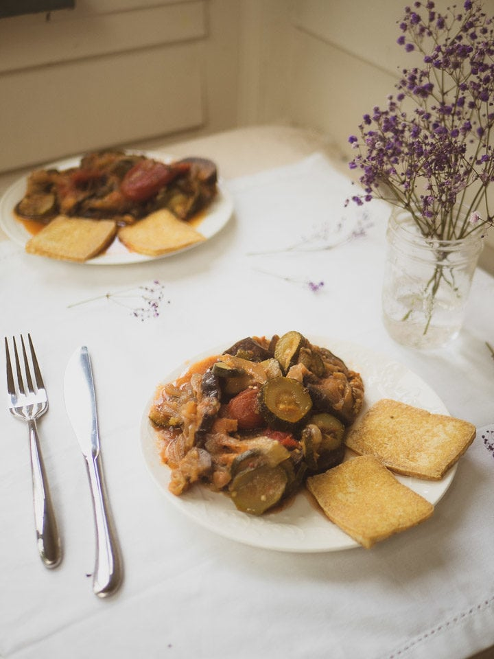 2 plates of instant pot ratatouille dish with pan-fried tofu on white table cloth and purple flowers