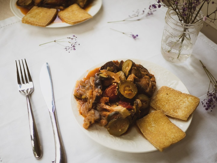Overhead look of instant pot ratatouille dish with pan-fried tofu on white table cloth
