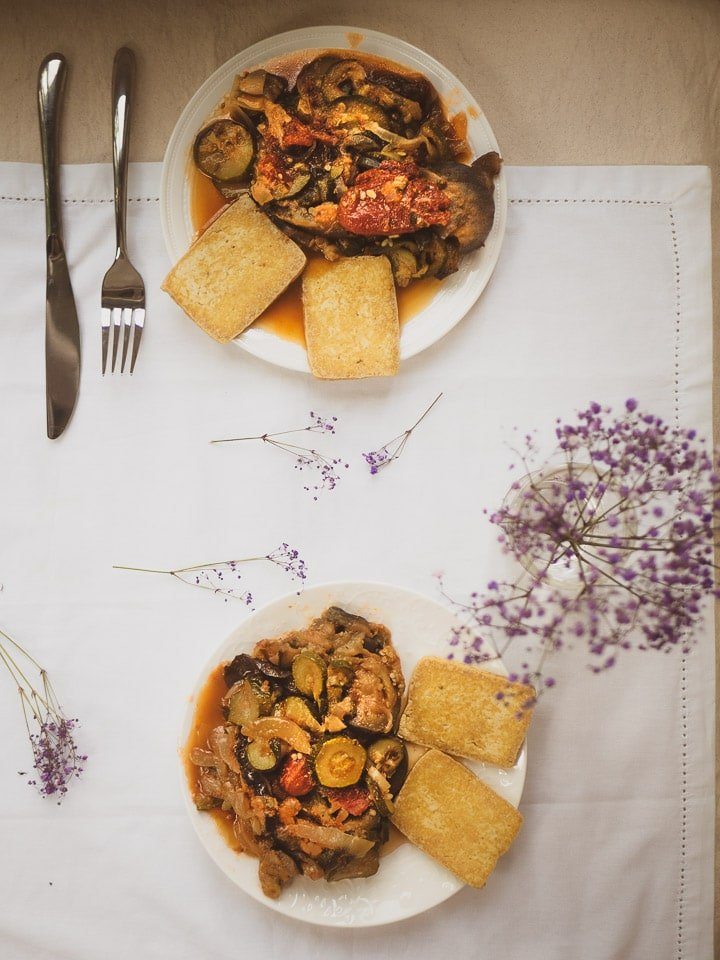 Overhead view of 2 plates of instant pot ratatouille dish with pan-fried tofu on white table cloth and purple flowers