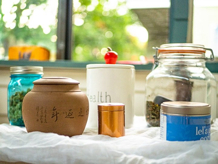 An assembly of all the tea containers including stoneware, glass, metal cans