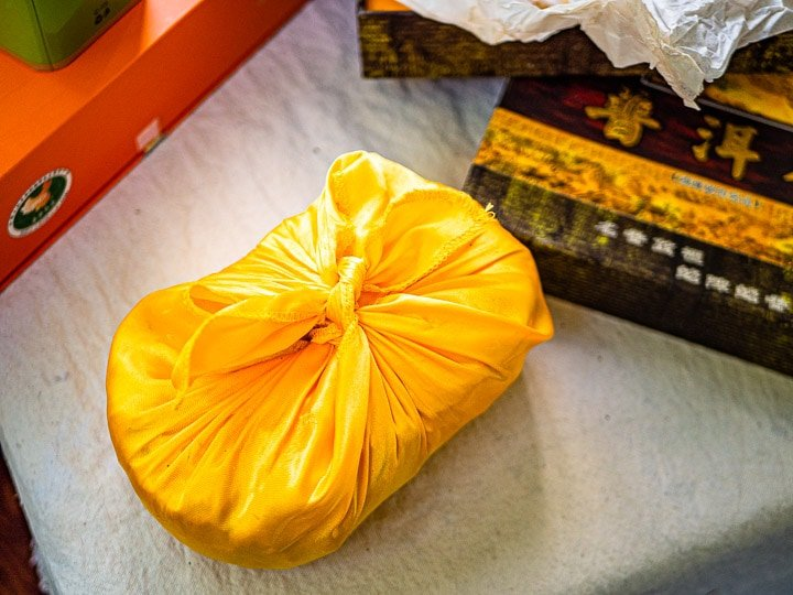 A close up look of pu'er tea wrapped in its packaging with yellow satin cloth