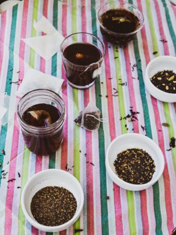 3 cups of tea with comparison of CTC tea, loose-leaf tea from a tea bag, and loose leaf tea with empty tea bags