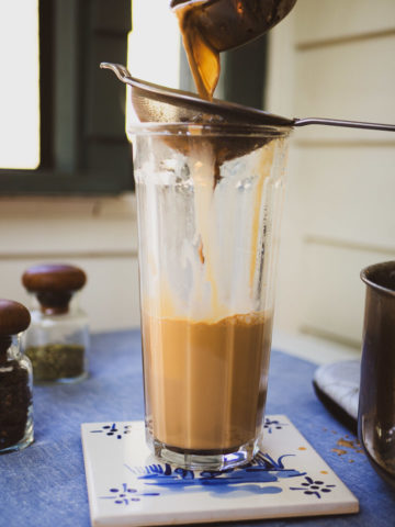 Pouring masala chai with a strainer to strain out the spices into a glass