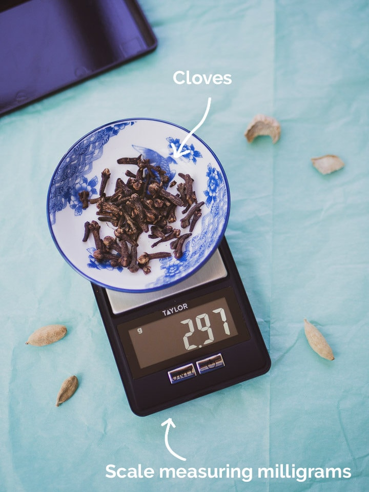 Scale for measuring milligrams to weigh the spices on a green background measuring a bowl of cloves