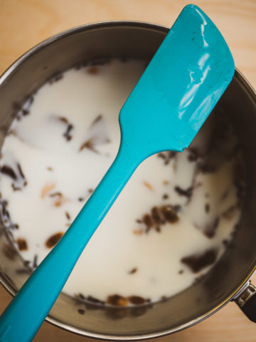 A overhead view of masala chai spices in a saucepan with milk and water with a spatula on top to avoid overspilling milk