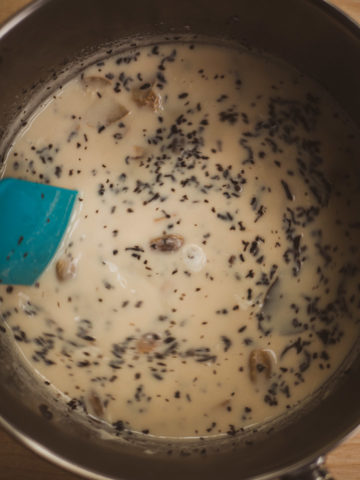 A overhead view of masala chai in a saucepan after mixing in the black tea