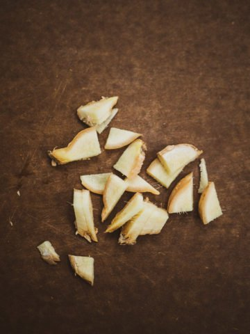Slices of ginger on a brown chopping board for the masala chai recipe