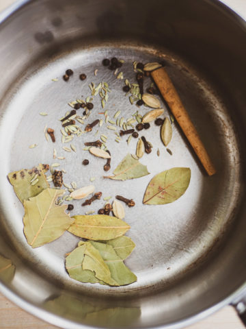 An overhead view of spices (peppercorns, green cardamom, cloves, fennel seeds, cinnamon, ginger, bay leaves) in a saucepan for toasting