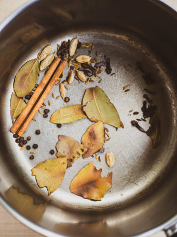 An overhead view of toasted spices (peppercorns, green cardamom, cloves, fennel seeds, cinnamon, ginger, bay leaves) in a saucepan for masala chai recipe