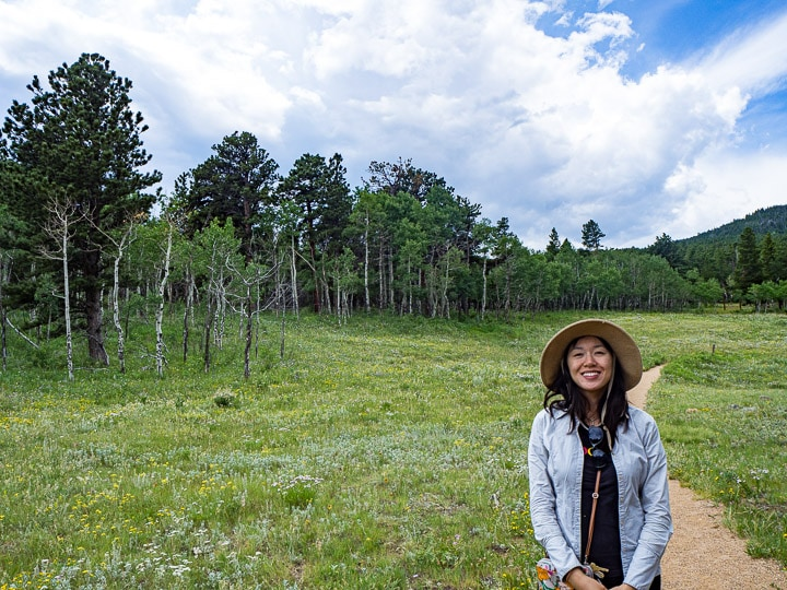 Anna in front of landscape view of Caribou Ranch Open Space in Nederland, CO with tall pine trees and open grassy areas