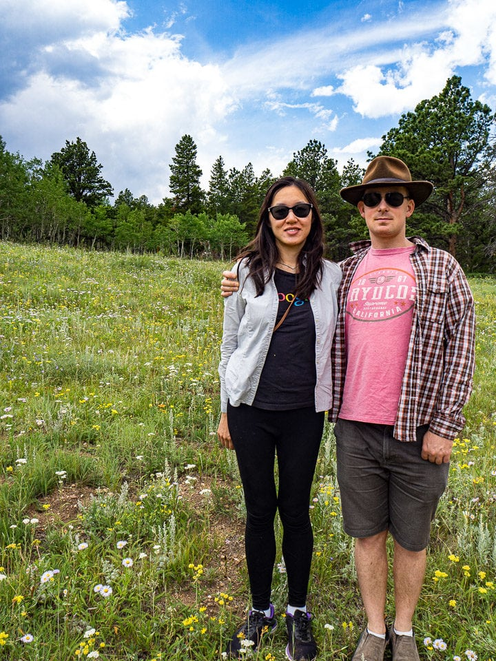 Anna and Alex at the Caribou Ranch Open Space in Nederland, CO in front of a field of wild flowers