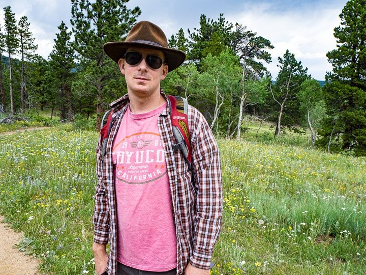 Alex at the Caribou Ranch Open Space in Nederland, CO in front of a field of wild flowers and trees