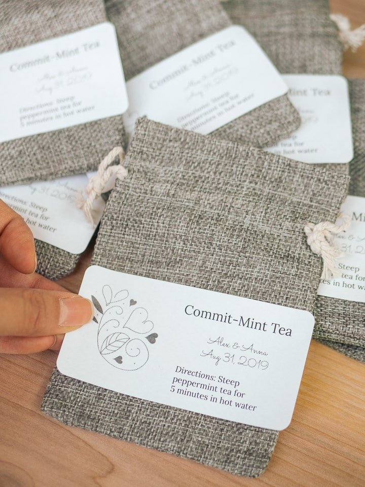 Close up look of applying a label to the burlap sack for the Garlic Delight wedding favors tutorial