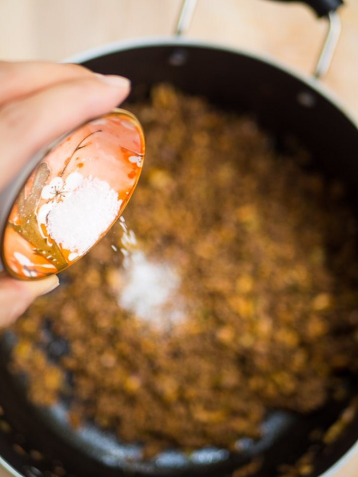 Overhead view of Anna's hand pouring salt into a pot of the Kari's Welcome Home Meat Sauce