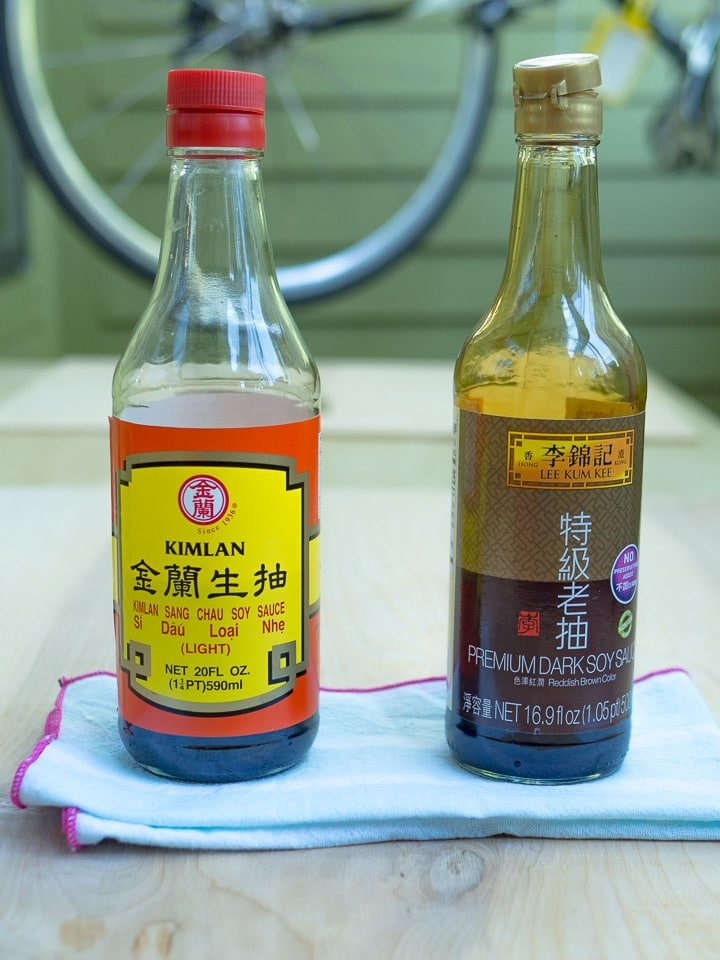 Side-by-side comparison of a bottle of dark soy sauce and light soy sauce on a wood surface