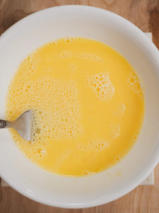 Anna's mixing raw eggs for the savory oatmeal recipe