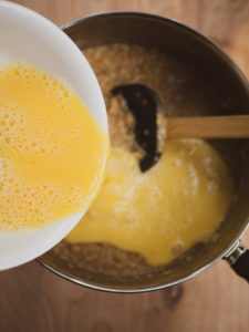 Anna's hand pouring mixed raw eggs into a sauce pot with cooked oatmeal for the savory oatmeal recipe