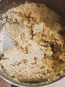 A close up look of cooked savory oatmeal with cooked egg in the savory oatmeal recipe