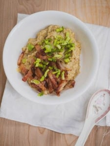 Sliced bacon with green onions on top of savory oatmeal for inspiration for savory oatmeal recipe